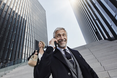 Portrait of smiling businessman on the phone with his business partner in the background - RORF01469