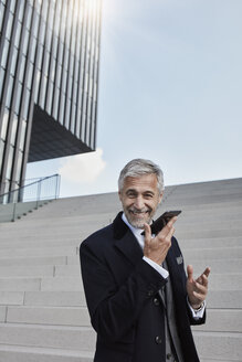 Portrait of content businessman on the phone standing in front of stairs - RORF01472