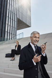 Portrait of businessman talking on mobile phone while business woman working on laptop in the background - RORF01475