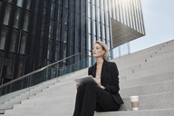 Blond businesswoman with tablet and coffee to go sitting on stairs in front of modern office building - RORF01478