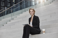 Portrait of smiling businesswoman with tablet and coffee to go sitting on stairs outdoors - RORF01481
