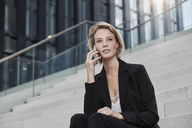 Portrait of young businesswoman on the phone sitting on stairs outdoors - RORF01484