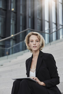Portrait of blond young businesswoman with tablet sitting on stairs outdoors - RORF01490