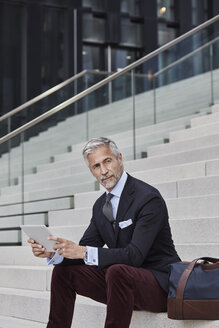 Portrait of fashionable businessman with travelling bag and tablet sitting on stairs - RORF01493