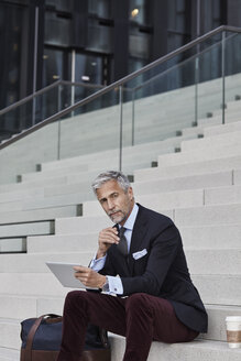 Portrait of fashionable businessman with travelling bag, coffee to go and tablet sitting on stairs - RORF01496