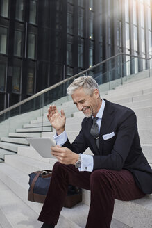 Fashionable businessman with travelling bag sitting on stairs using tablet - RORF01499