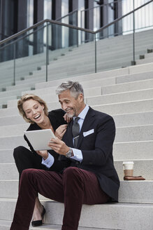 Portrait of two businesspeople sitting together on stairs looking at tablet having fun - RORF01502