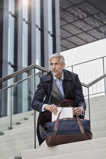 Portrait of mature businessman with traveeling bag and tablet crouching on stairs outdoors - RORF01508