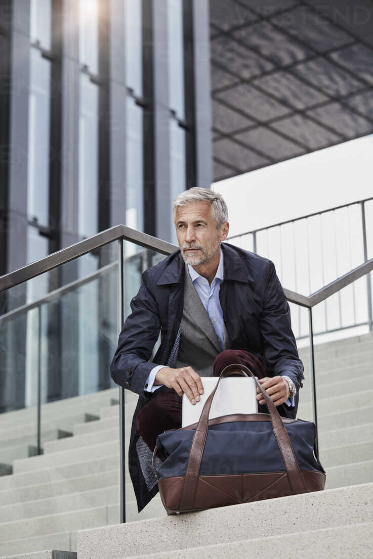 Portrait of mature businessman with traveeling bag and tablet crouching on stairs outdoors - RORF01508 - Roger Richter/Westend61