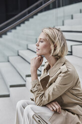 Young blond businesswoman wearing beige trenchcoat sitting on stairs - RORF01523