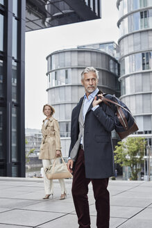 Germany, Duesseldorf, two fashionable business people with traveling bags - RORF01532