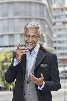 Germany, Duesseldorf, portrait of laughing mature businessman talking on mobile phone - RORF01535