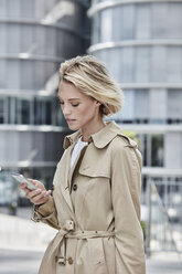 Germany, Duesseldorf, portrait of  blond businesswoman wearing beige trenchcoat looking at cell phone - RORF01538
