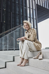 Portrait of laughing young blond woman with digital camera sitting barefoot on stairs - RORF01544