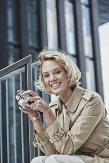 Portrait of smiling young blond woman with digital camera sitting on stairs - RORF01547