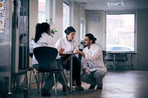 Multi-ethnic chefs discussing menu in restaurant - MASF08635