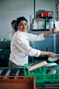 Portrait of confident female chef washing plate in kitchen - MASF08644