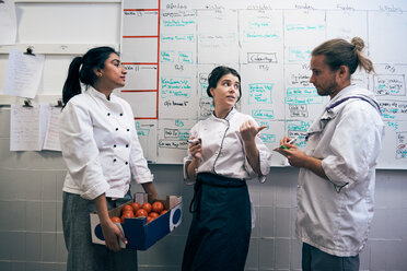 Chefs communicating against whiteboard in kitchen - MASF08653