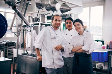 Portrait of multi-ethnic chefs standing in commercial kitchen - MASF08656