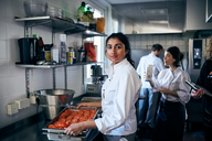 Portrait of chef with tomatoes in baking sheet at commercial kitchen - MASF08665