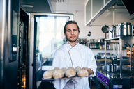 Portrait of chef baking breads in commercial kitchen - MASF08668