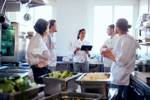 Mid adult female chef holding digital tablet while discussing with team in kitchen - MASF08674