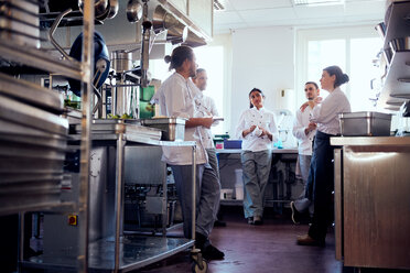 Male and female chefs having discussion in commercial kitchen - MASF08677