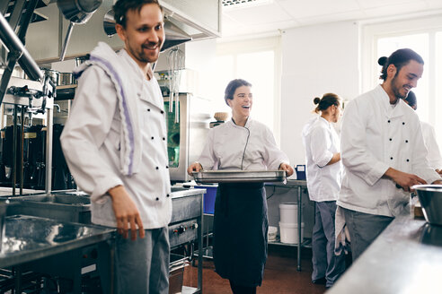 Smiling female chef with colleagues working in commercial kitchen - MASF08695
