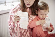 Mother and daughter with financial bills at home - MASF08710
