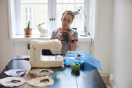 Tailor sewing scarf on machine while sitting against window at home - MASF08719