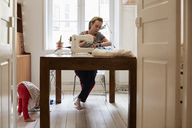 Tailor sewing at table while daughter playing on floor seen through doorway at home - MASF08722