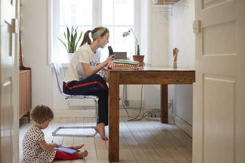 Podcaster talking on microphone while daughter using digital tablet at home - MASF08737