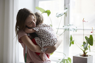 Female fashion designer embracing daughter while standing by window at home - MASF08743