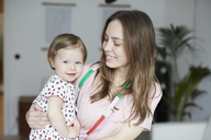 Female fashion designer with tape measure carrying daughter at home - MASF08746