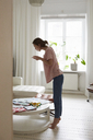 Full length side view of fashion designer photographing fabric at home - MASF08752