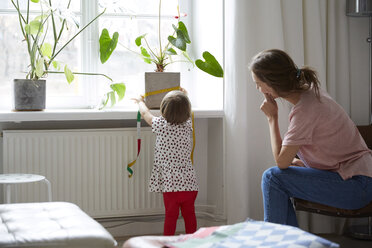 Fashion designer looking at daughter measuring potted plant with tape measure - MASF08755