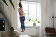 Full length of fashion designer measuring curtain while daughter playing on sofa at home - MASF08758