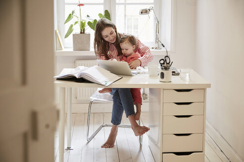 Female accountant sitting with daughter while working on laptop at home - MASF08764