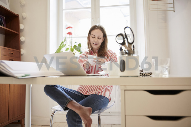 Full length of young woman examining financial bill while working from home - MASF08767