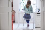 Girl standing behind door while mother working on laptop in background at home - MASF08773