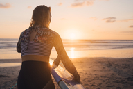 Rear view of woman with surfboard walking towards sea at beach during sunset - MASF08776