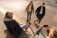 High angle view of teenage boy photographing friends skateboarding at park - MASF08815