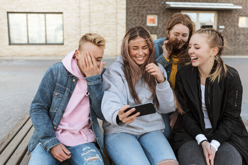 Smiling teenage girl taking selfie with friends through smart phone in city - MASF08824