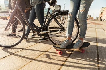 Low section of boy skateboarding with friends and bicycle on footpath - MASF08830