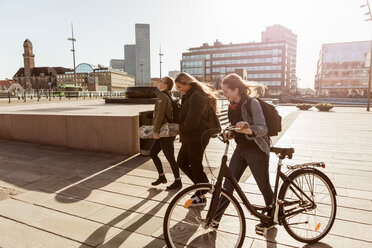 Teenage girl holding bicycle while walking with friends on pedestrian zone in city - MASF08833