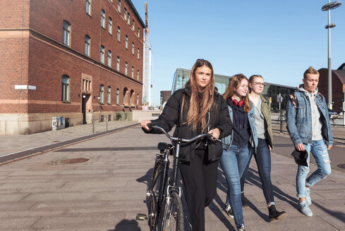 Teenage girl holding bicycle while walking with friends on footpath in city against clear sky - MASF08839