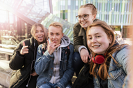 Happy teenage friends taking selfie in city - MASF08842