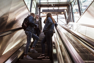 Low angle view of teenage friends talking while standing on escalator - MASF08854