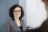 Portrait of smiling confident businesswoman wearing eyeglasses at office - MASF08860
