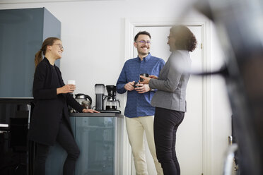 Smiling business colleagues having coffee while talking at office - MASF08863